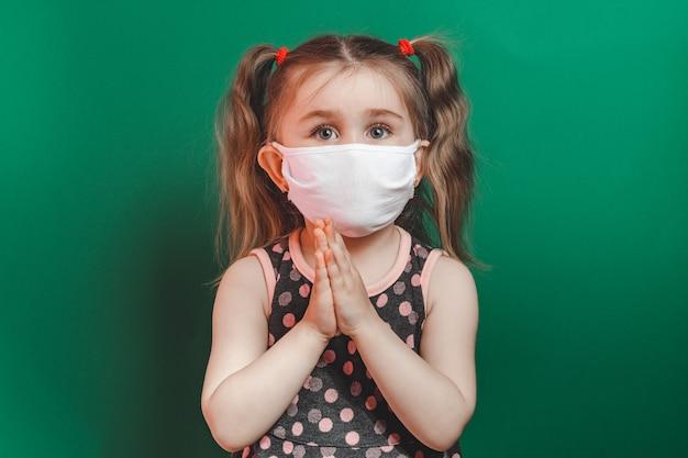 Caucasian sick little girl in medical mask during coronavirus epidemic prays on green background closeup.