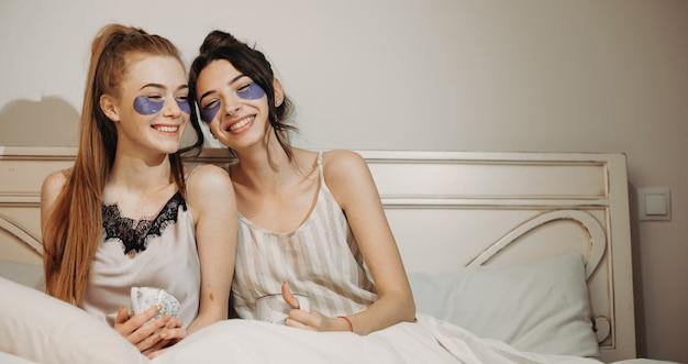 ベッドに座ってお茶を飲みながら目の下にしわ防止マスクを着用している白人の姉妹