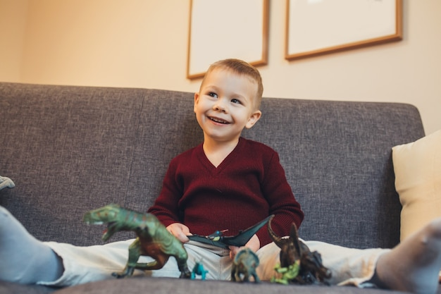 Caucasian small boy sitting on the sofa and playing with his dinosaur toys while looking at his parents