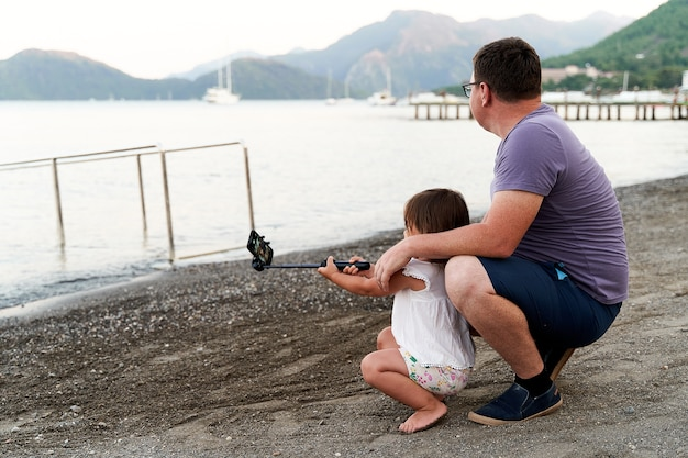 Caucasian small girl with dad with selfie stick on the seaside. taking photo, recording vlog, video call