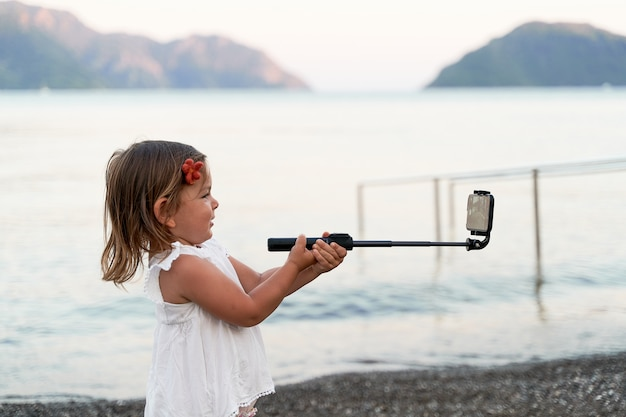 Caucasian small girl with selfie stick on the seaside. taking photo, recording vlog, video call