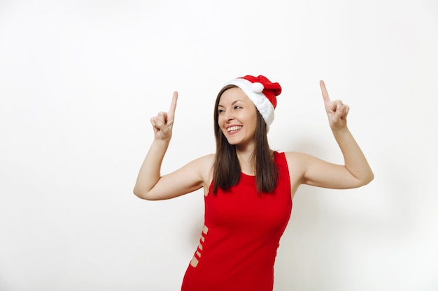 Кавказская улыбка счастливая женщина в красном платье и рождественская шляпа, указывая вверх ногами с пальцами на обеих руках на белом фоне. изолированная девушка санты. новый год праздник 2018. копирование места для рекламы