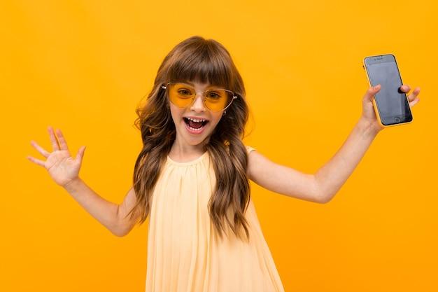 Кавказская улыбающаяся девушка в очках раскидывает руки в стороны и держит телефон на желтом фоне.