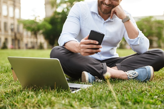 Caucasian smiling man in business clothing, sitting on grass in park with legs crossed while using cell phone and silver laptop