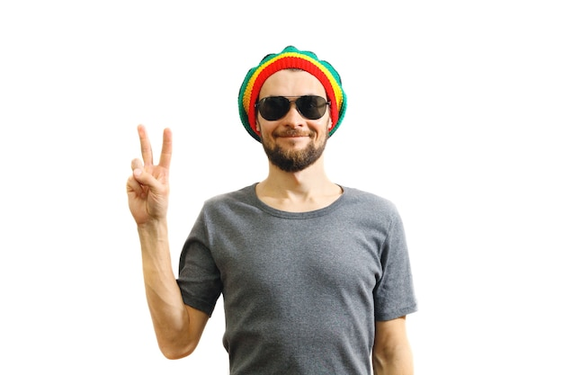 Caucasian smiling man in rasta hat sunglasses and grey tshirt on white background peace gesture