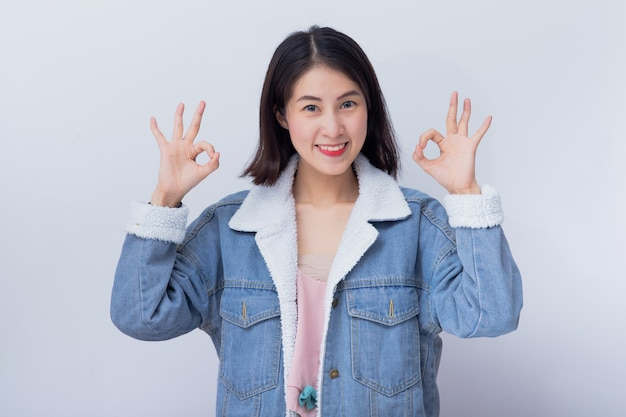 Caucasian smiling woman showing her hand with ok sign,  positive happy young asian girl wearing blue casual clothes portrait