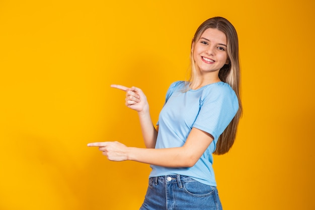 Caucasian smiling young woman pointing with two fingers to the side with free space for text.