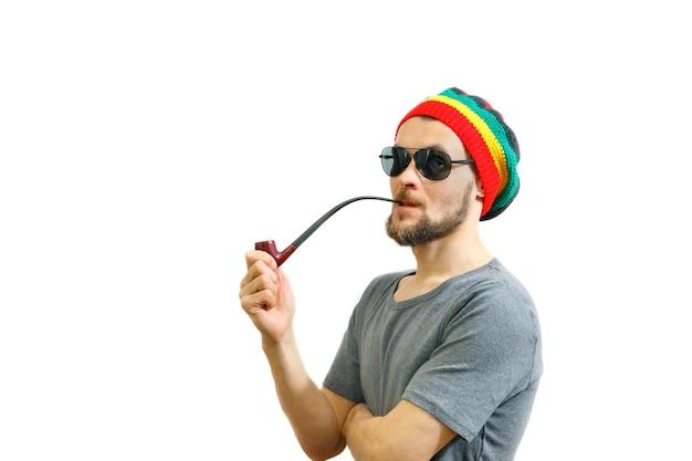 Caucasian smoker man in rasta hat sunglasses and grey tshirt on white background with smoke pipe