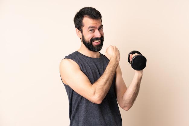 Кавказский спортивный человек с бородой, делая тяжелую атлетику, празднует победу