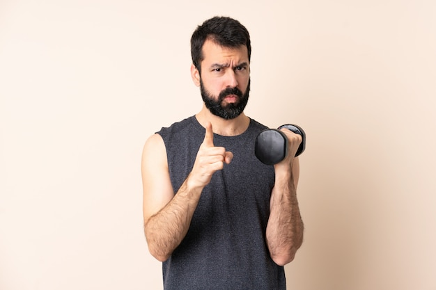 Caucasian sport man with beard making weightlifting over isolated space frustrated and pointing to the front