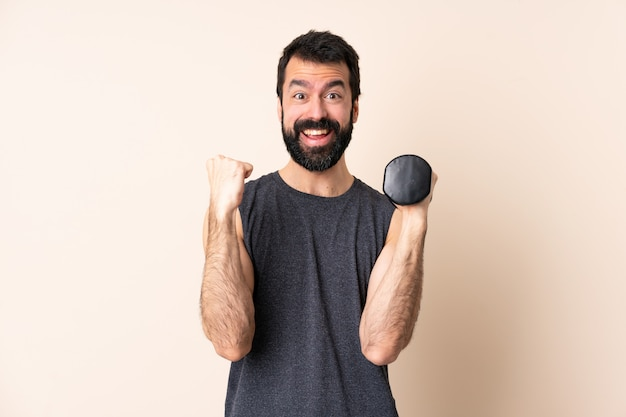 Caucasian sport man with beard making weightlifting over isolated wall celebrating a victory in winner position
