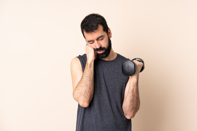 Caucasian sport man with beard making weightlifting over isolated with tired and bored expression