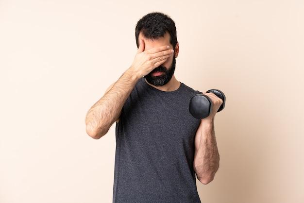 손으로 눈을 덮고 격리 된 배경 위에 역도를 만드는 수염을 가진 백인 스포츠 남자