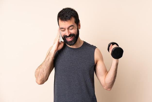누군가와 휴대 전화로 대화를 유지하는 격리 된 배경 위에 역도를 만드는 수염을 가진 백인 스포츠 남자