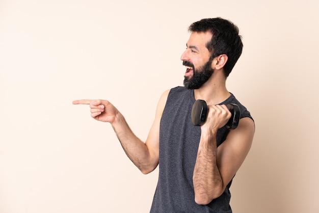横に指を指し、製品を提示する孤立した背景の上に重量挙げを作るひげを持つ白人スポーツ男