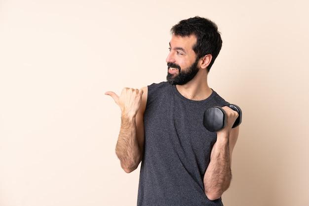 製品を提示する側を指している孤立した背景の上に重量挙げをしているひげを持つ白人スポーツ男
