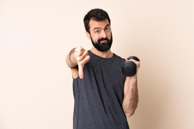 Кавказский спортивный человек с бородой делает тяжелую атлетику на изолированном фоне, показывая большой палец вниз с отрицательным выражением лица