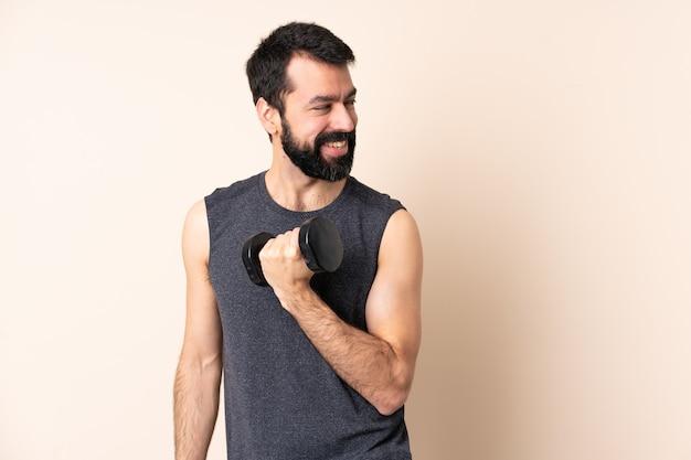 腕を組んで幸せな孤立した背景の上に重量挙げを作るひげを持つ白人スポーツ男