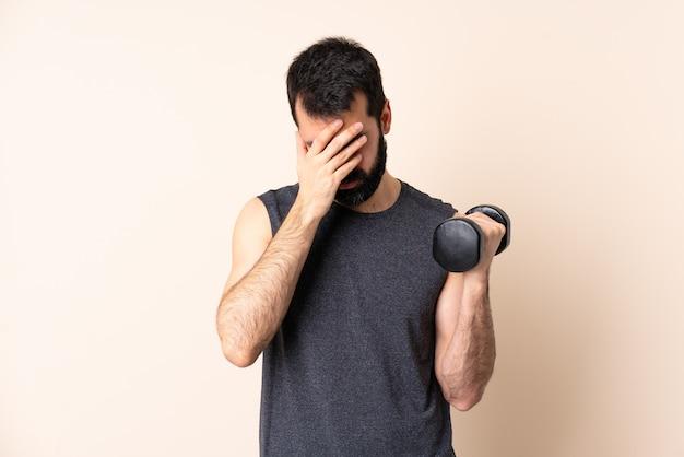 피곤하고 아픈 표정으로 격리 된 배경 위에 역도를 만드는 수염을 가진 백인 스포츠 남자