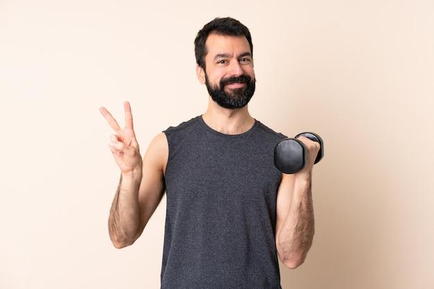 Кавказский спортивный человек с бородой, делая тяжелую атлетику над изолированным пространством, показывая знак победы обеими руками