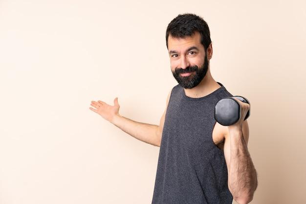 髭を生やした白人スポーツマンが、孤立した壁を越えて重量挙げをし、手を横に伸ばして招待