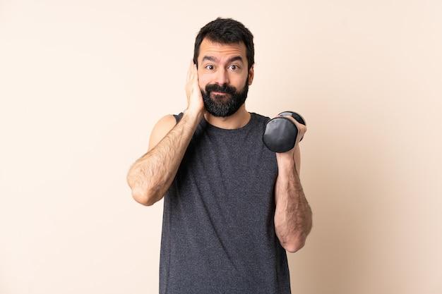 欲求不満と耳を覆っている孤立した壁の上に重量挙げをしているひげを持つ白人スポーツ男