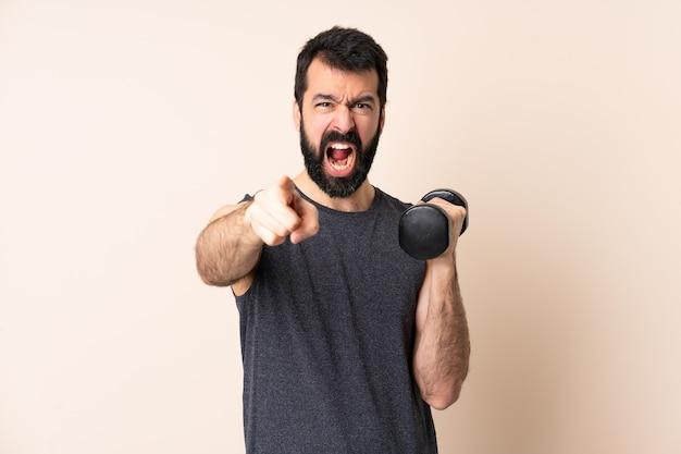 Кавказский спортивный мужчина с бородой делает тяжелую атлетику над изолированной стеной, разочарованный и указывая вперед