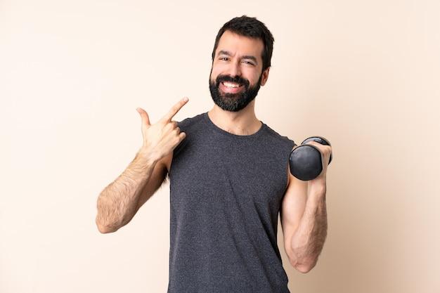 제스처를 엄지 손가락을주는 고립 된 벽에 역도를 만드는 수염을 가진 백인 스포츠 남자
