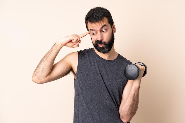 Кавказский спортивный мужчина с бородой делает тяжелую атлетику над изолированной стеной, делая жест безумия, положив палец на голову