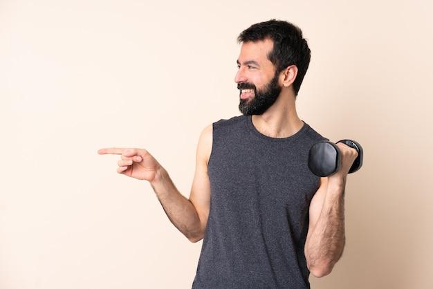 横に指を指している孤立した壁の上に重量挙げを作るひげを持つ白人スポーツ男