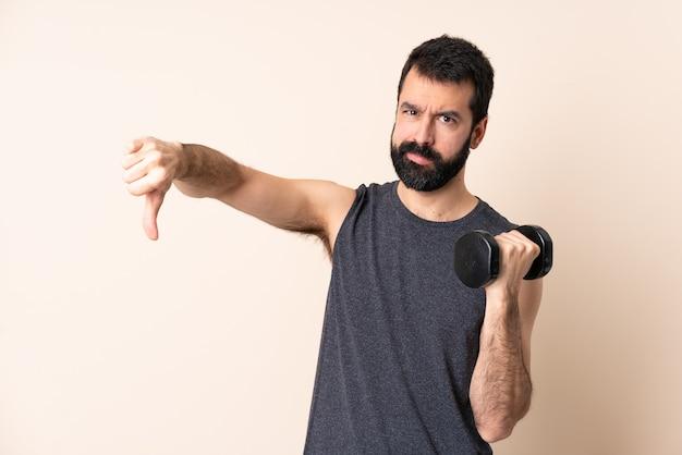 否定的な表現で親指を下に示す孤立した壁の上に重量挙げをしているひげを持つ白人スポーツ男
