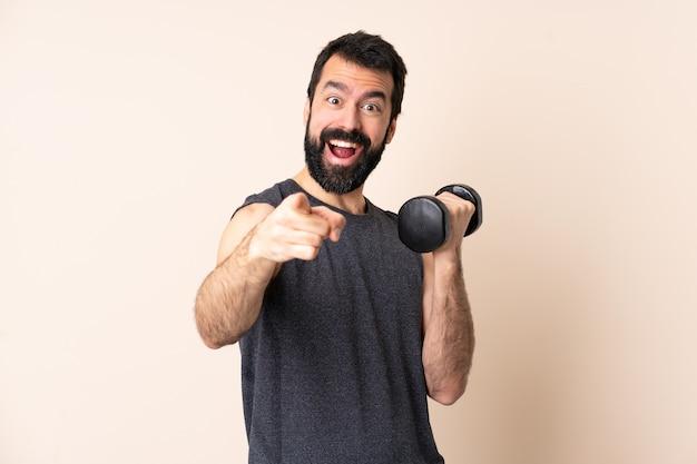 髭を生やした白人スポーツ男が孤立した壁に重量挙げを驚かせ、正面を向いている