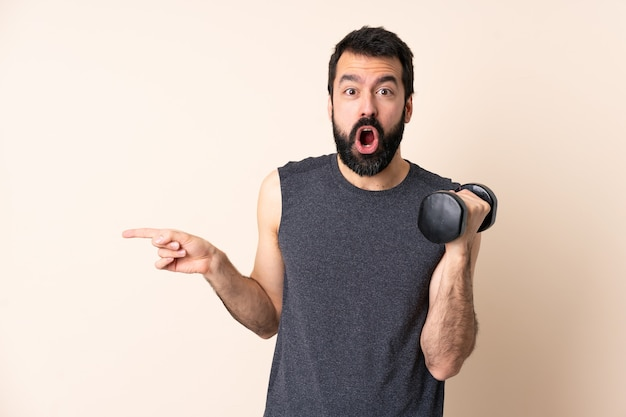 髭を生やした白人スポーツ男が孤立した壁に重量挙げを驚かせ、側を指しています