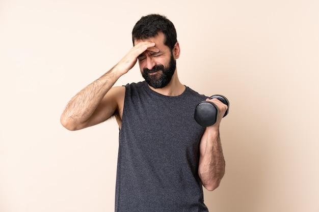 頭痛で孤立した壁に重量挙げをするひげを持つ白人スポーツ男