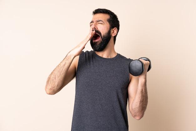 Кавказский спортивный человек с бородой делает тяжелую атлетику на стене зевая и прикрывая широко открытый рот рукой