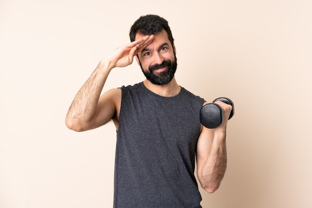 Caucasian sport man with beard making weightlifting saluting with hand with happy expression