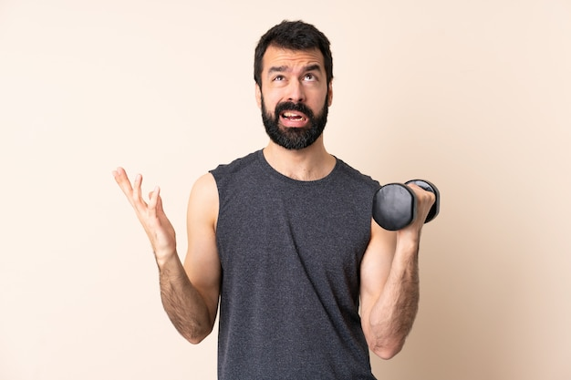 Caucasian sport man with beard making weightlifting over wall stressed overwhelmed
