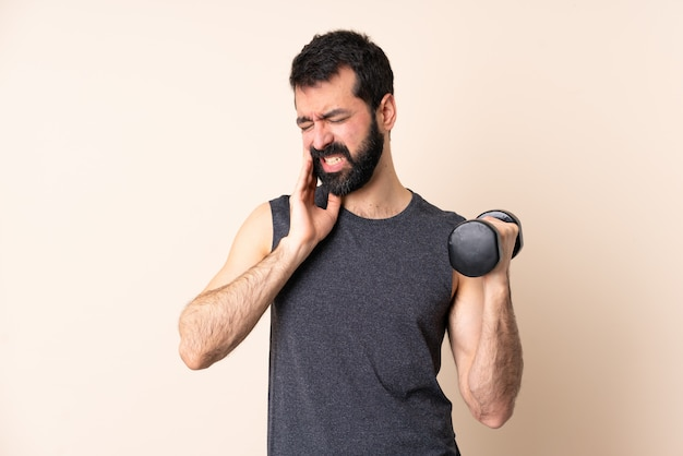Caucasian sport man with beard making weightlifting over wall with toothache