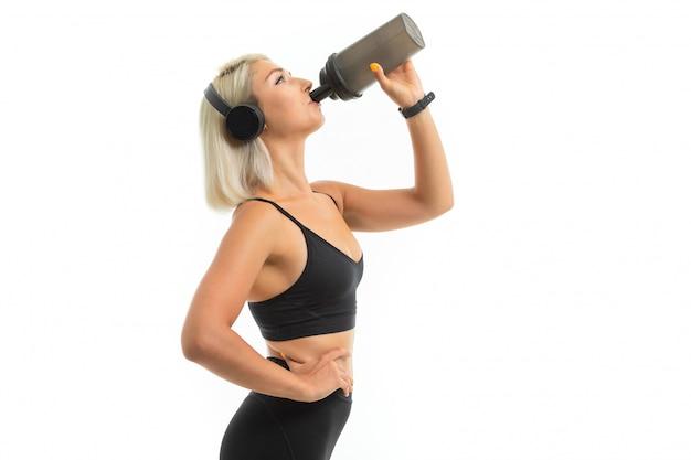 ブロンドの髪を持つ白人スポーツ女性は大きなイヤホンで音楽を聴くし、スポーツボトルで水を飲む