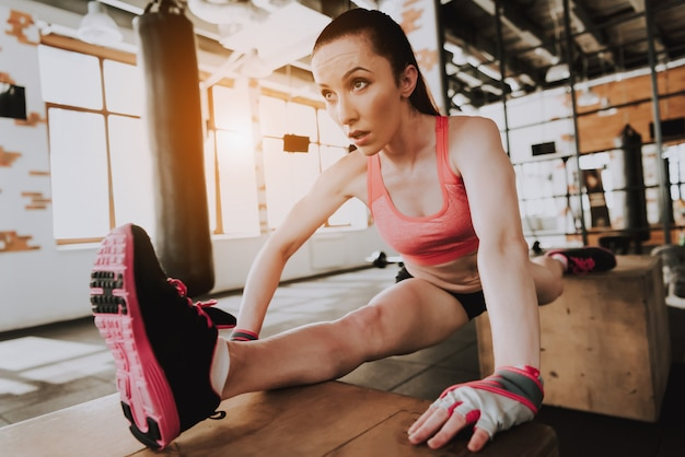 Caucasian sportswoman is exercising in gym alone
