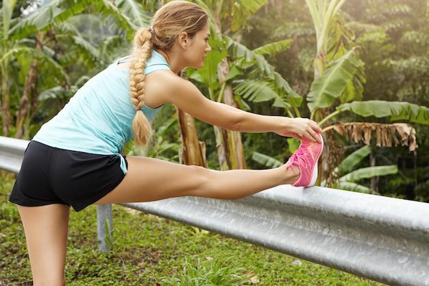 三つ編みを伸ばして脚を温め、長い目で見る前に筋肉を準備する白人のスポーツウーマン。