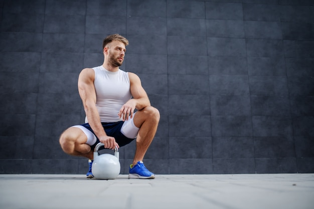 Caucasian sporty muscular man posing, crouching and holding kettle bell outdoors.