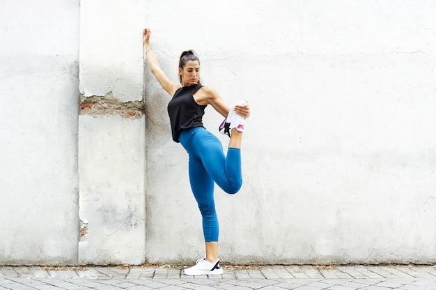 通りでトレーニングしている白人のスポーティーな女性
