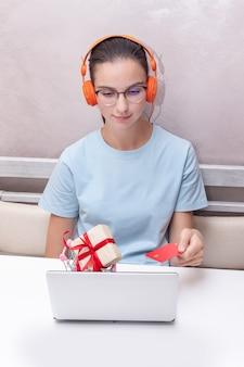 온라인 학습 과정, 수직 프레임을 구입하기 위해 노트북을 사용하여 신용 카드를 들고 테이블에 앉아있는 백인 학생 소녀. 그 소녀는 신용 카드와 노트북을 사용하여 인터넷에서 쇼핑합니다.