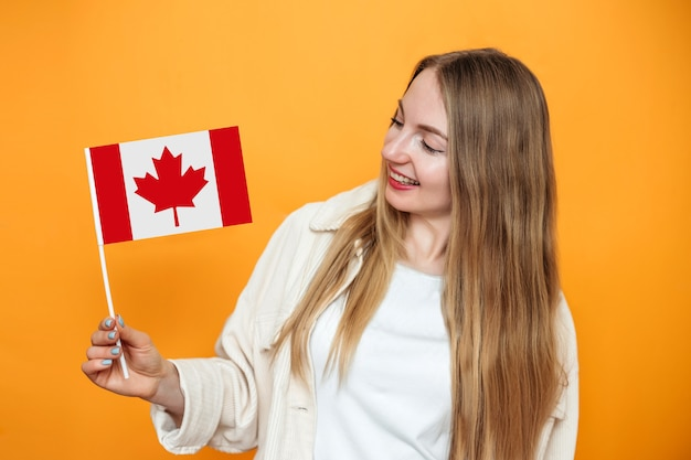Caucasian student girl smiling and holding a small canada flag and looking to camera isolated over orange background, canada day, holiday, confederation anniversary, copy space