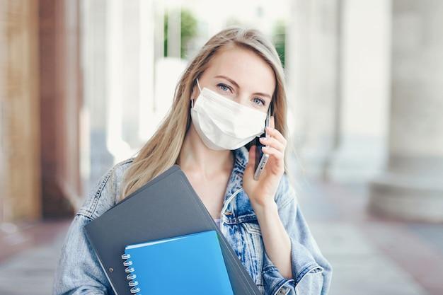 医療用マスクを身に着けている白人の学生の女の子が大学の前に立ち、コロナウイルスの検疫中に携帯電話で話しているcovid-19