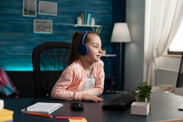 Caucasian student wearing headphones on online class using computer and internet connection at home desk. smart little child attending elementary school lesson looking at monitor learning