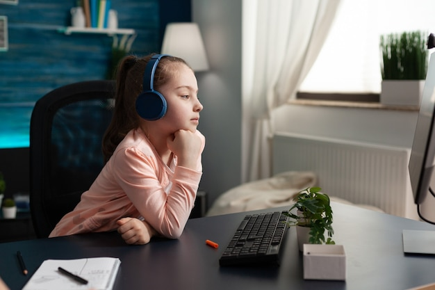 Caucasian student wearing headphones on online class