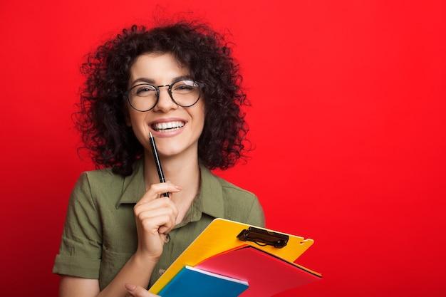 巻き毛の黒い髪と眼鏡を持つ白人の学生は、赤い背景でポーズをとっている間、ペンといくつかの本を持っています