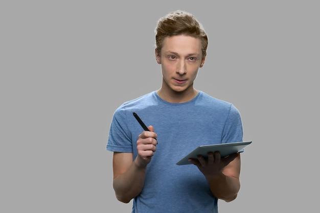 디지털 태블릿에 노력하는 백인 학생. 스타일러스 펜을 사용하여 태블릿 장치에 메모를 만드는 사려 깊은 표정으로 스마트 10 대 소년.